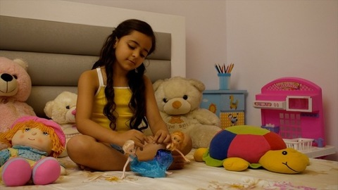 Active playful cute child girl playing with two dolls while seated isolated on the bed in her room - Happy Childhood