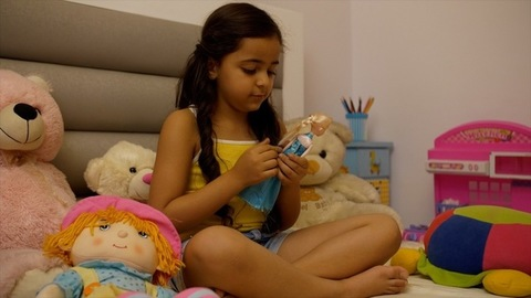 Cute playful little child girl playing with toys at home - making a braid of her favorite doll