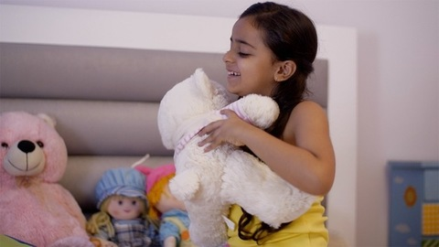 Cheerful little child girl playing with a teddy bear in the bedroom - child play concept