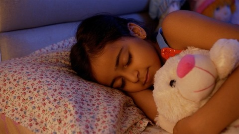Portrait of a cute little child girl sleeping and holding a teddy bear at night