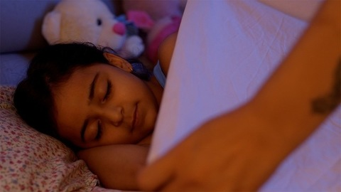 Cute young Indian girl sleeping and her mother covering her with a blanket