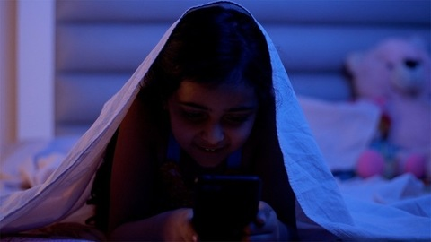 Smiling young girl watching videos on her smartphone at night - hiding under the blanket, static camera