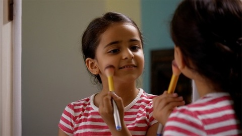Pretty child girl standing in front of the mirror and applying makeup with a fluffy brush