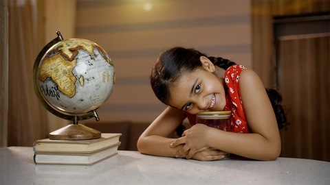 Smiling little Indian child girl collecting coins, money in a clear glass jar in study room - saving concept