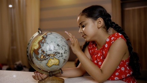 Thoughtful little Indian child preschooler looking and playing with a world globe in the study room