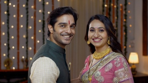 Young Indian couple happily smiling looking into the camera in traditional wear