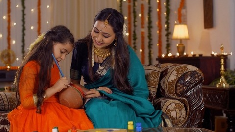 Indian mother and daughter painting a clay pot together - Motherhood Concept