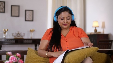 Indian woman listening to music and enjoying reading a novel - Pleasure time spending