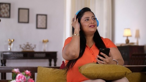 Indian woman listening to songs and enjoying while sitting on a couch in her living room