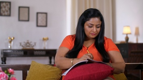 Indian woman working on an official assignment at home - Sitting on the couch and working from home