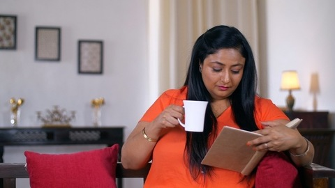Indian woman sitting on a couch and reading a book - Education and Reading Concept