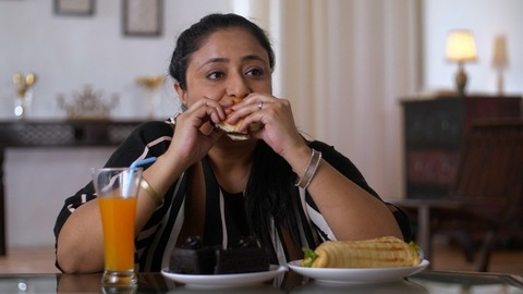 Indian fat woman consuming an appetizing food - Unhealthy food Concept