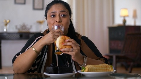 Indian overweight woman eating a burger at home - Junk and unhealthy food
