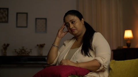 The distressed Indian woman sitting on a couch in the dark room - Strong emotions