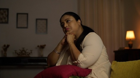 Indian overweight woman sitting on a couch and thinking -  loneliness concept