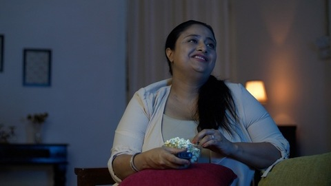 Overweight female taking a handful of popcorn and eating in front of the TV at home - Sedentary and unhealthy lifestyle