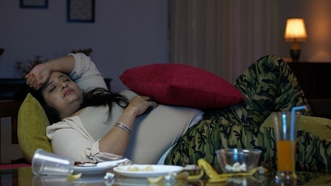 Overweight Indian woman relaxing on a couch after eating - Unhealthy lifestyle