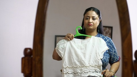 Indian woman viewing her reflection and upsets about her physique - health concept
