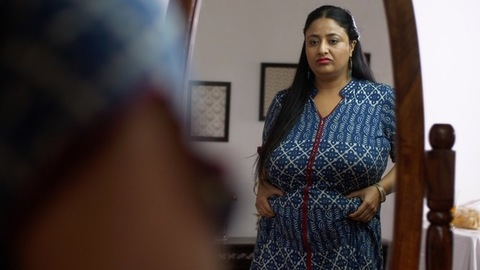 Indian overweight woman pinching her belly fat with frowning gesture - weight  control concept