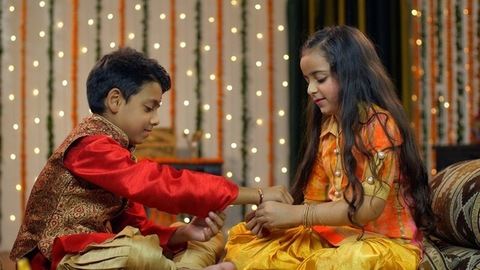 Cute sister celebrating Raksha Bandhan with her sweet little brother - festive season