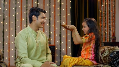 Young Indian siblings happily performing Raksha Bandhan / Bhai Dooj traditions