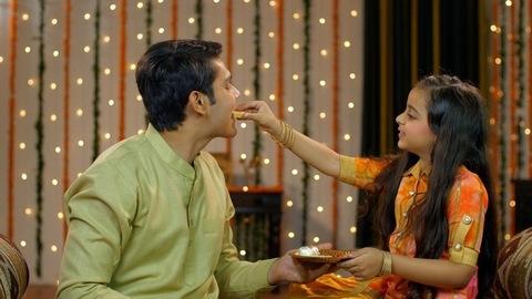 Happy siblings sharing sweets on the occasion of Raksha Bandhan / Bhai Dooj