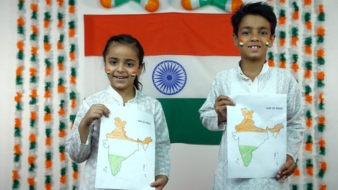 School going boy and a girl standing with Indian map - India celebrates Independence day.  Patriotism concept