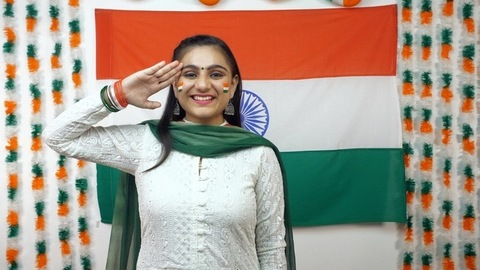 Young Indian girl saluting the nation and looking towards the camera - Independence Day Concept