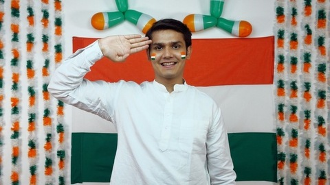 Indian boy salutes facing towards the camera. Tricolor background - Independence Day
