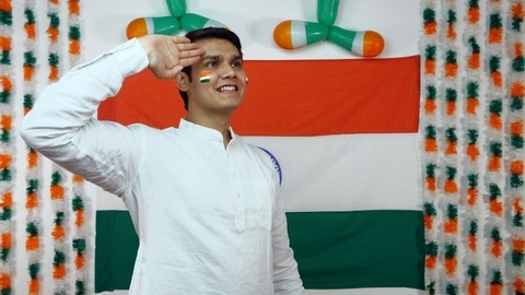 Young Indian boy saluting at the Indian national flag - Republic day concept