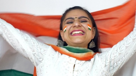 Close shot of a beautiful Indian woman proudly holding a national flag - Independence Day / Republic Day concept