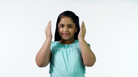 Cute little girl smiling with hands close to her face in a blue top - white background
