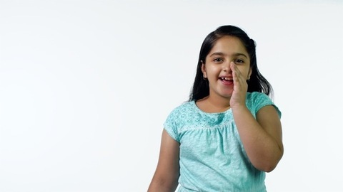 Beautiful young girl whispering her secrets against the white background