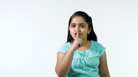 Cute Indian girl putting finger on her lips and asking not to tell anyone her secrets