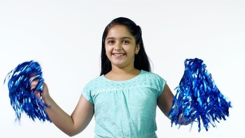 A young pretty cheerleader shaking her blue pom-poms with a smile on her face