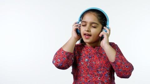A cute little girl enjoying music using her Bluetooth headphones - technology concept