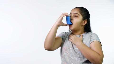 Young Indian girl using an inhaler for asthma and other respiratory diseases