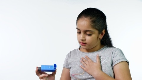 Young asthma patient using a medical spray to treat asthma attack against the white background