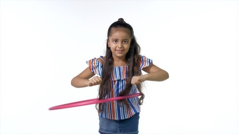 Talented little girl in casual wear playing with a hula hoop against the white background