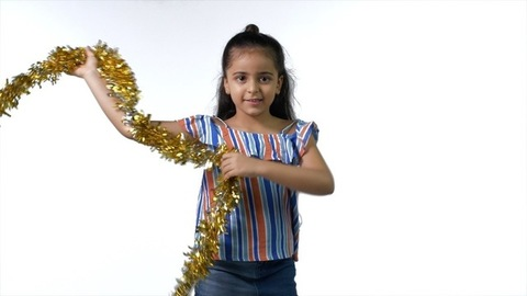Cute Indian girl happily dancing with a party prop against the white background