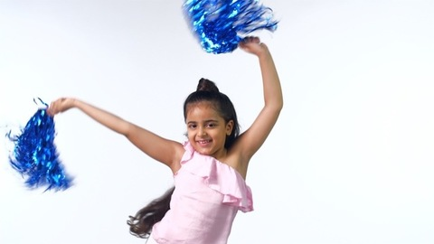 A young pretty cheerleader happily smiling and waving her blue pom-poms