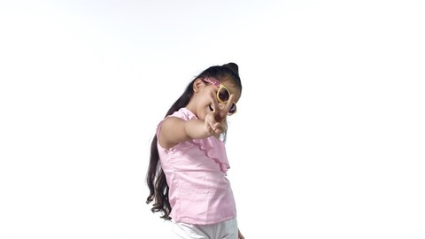Cute Indian girl in yellow sunglasses happily showing peace sign in trendy casual wear