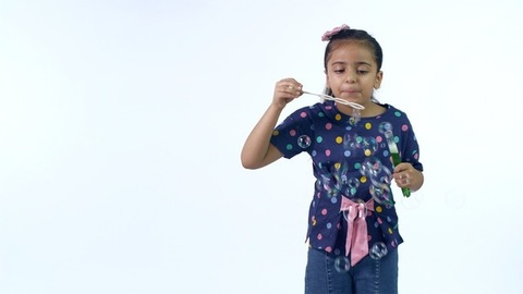Attractive Indian girl happily blowing soap bubbles on a white background - leisure concept