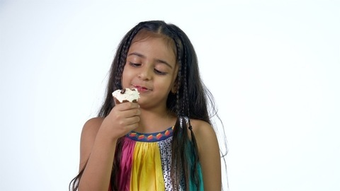 A cute little girl enjoying her delicious ice cream in colorful and trendy casual wear