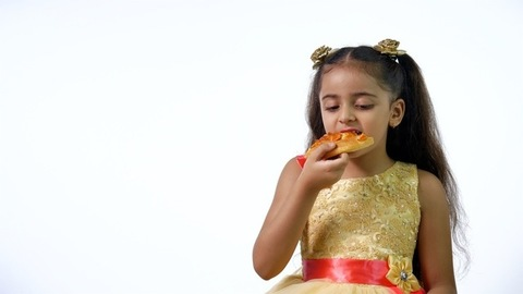 A cute little girl from India eating a pizza slice against the white background - junk food, unhealthy food