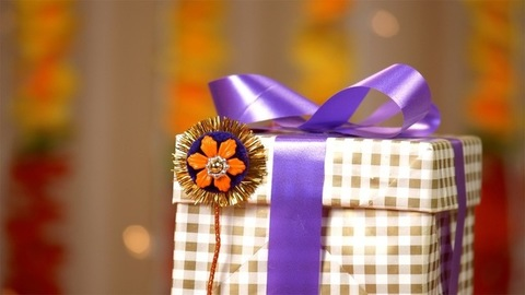 A beautiful shot of a handmade rakhi and a wrapped gift for Raksha Bandhan
