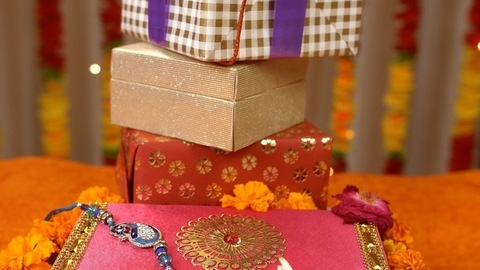 Different Raksha Bandhan Items placed on one another with a beautiful rakhi on the top