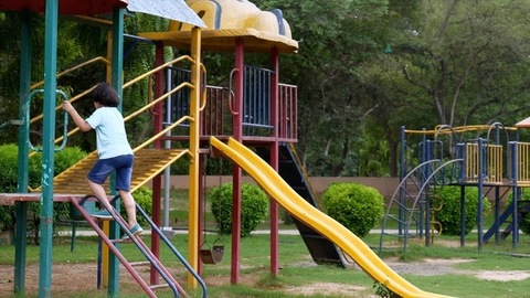 A young handsome kid with long hair climbing on a colorful swing - evening playtime