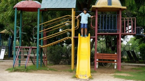 Young cheerful boy climbing and sliding on a swing of kids zone area in a school park