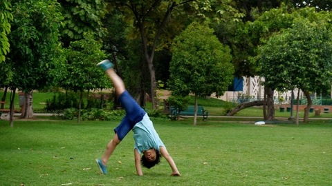 The young gymnastic boy happily doing cartwheels in a park - fun outdoor activities